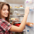 Girl putting snack into refrigerato - 图库照片