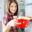 Girl eating soup from pan near fridge — Stock Photo