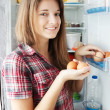 Girl putting eggs into refrigerato - Stock Photo