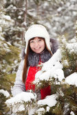 Woman in wintry pine forest — Stock Photo