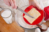 Cook hands adds margarine into dough — Stock Photo