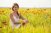 Girl is sitting on flowers meadow — Stock Photo