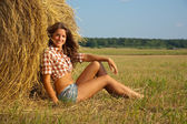 Girl on fresh straw — Stock Photo