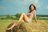 Girl in checked shirt on straw — Stock Photo