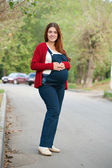 Pregnant woman stands on street — Stock Photo