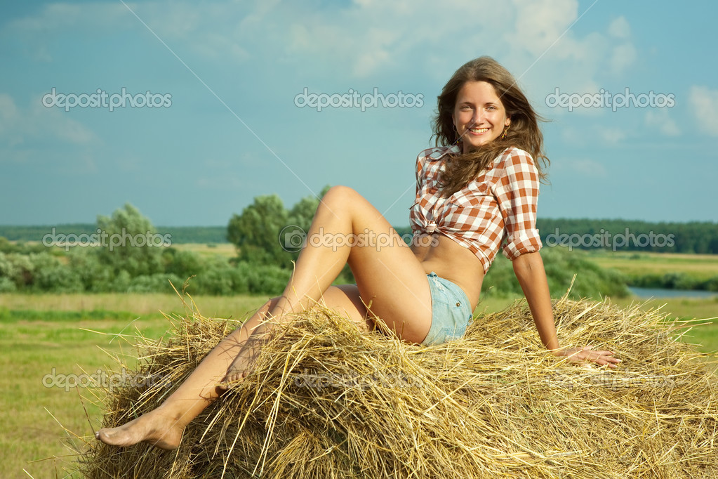 Pretty girl in checked shirt resting on straw bale  Stock Photo #5152682