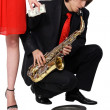 Girl alms to a man who plays the sax - Stock Photo