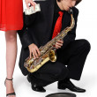 Girl alms to a man who plays the sax — Stock Photo