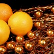 Oranges over gold Christmas balls — Stock Photo