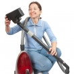 Smiling Woman vacuuming — Stock Photo