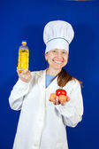 Female cook with different foods — Stock Photo