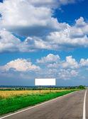 Billboard and long road — Stock Photo