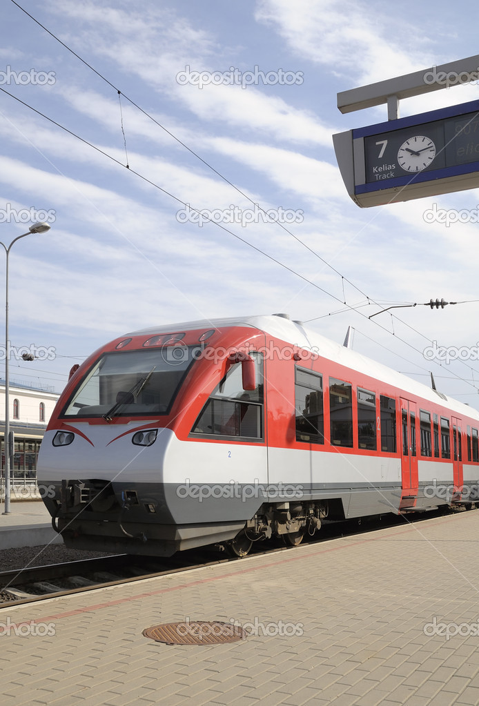Modern train at railway station in expectation of departure against the sky with plumes clouds — Stock Photo #3566613