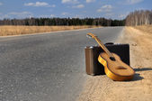 Baggage and guitar on empty road — Stock Photo