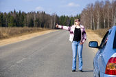 R girl hitchhiking on the — Stock Photo