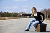 Country girl hitchhiking on the road — Stock Photo