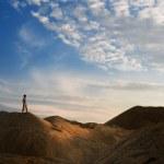 Young man in sand desert in sundown silhouette — Stock Photo
