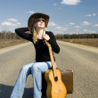 Country girl with guitar sits on road solitary — Stock Photo