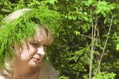 Beautiful young girl wearing floral wreath closeup — Stock Photo