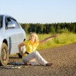Girl sitting and signaling problems with car — Stock Photo #3422000