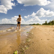 Young boy running at the beautiful beach — Stok fotoğraf