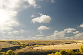 Big sun cloudy blue sky above an autumn landscape — Stock Photo