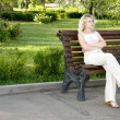Beautiful sad young woman sitting on the bench — Stock Photo #3476242