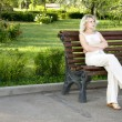 Beautiful sad young woman sitting on the bench — Stock Photo