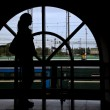 Foto de Stock  : Silhouette womopposite window railway station