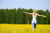 Happy young woman is standing on a field — Stock Photo