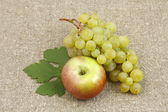 Bunch of white grapes and apples on a background of the matting — Stock Photo