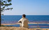 De man zit op de oever van de zee — Stockfoto
