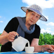 The woman pours milk from a jug in a mug — Stock Photo