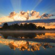 Sunrise and reflection in river — Stock Photo