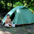 Smiling boy near camping tent — Stock Photo