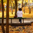 Girl on bench in autumn park - Stock Photo