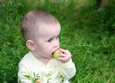 Small baby biting apple — Stock Photo