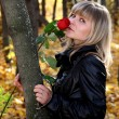 Girl with rose in autumn park - Stock Photo