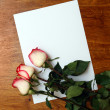 Roses and blank paper on table — Foto Stock