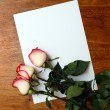 Roses and blank paper on table — Stock Photo