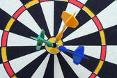 Dartboard with darts in aim — Stock Photo