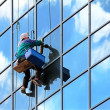 Window cleaner hanging on rope at work on skyscraper — Stock Photo #3714135