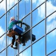 Stock Photo: Window cleaner hanging on rope at work on skyscraper