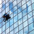 Royalty-Free Stock Photo: Window cleaner hanging on rope at work on skyscraper