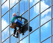 Window cleaner hanging on rope at work on skyscraper — Stock Photo
