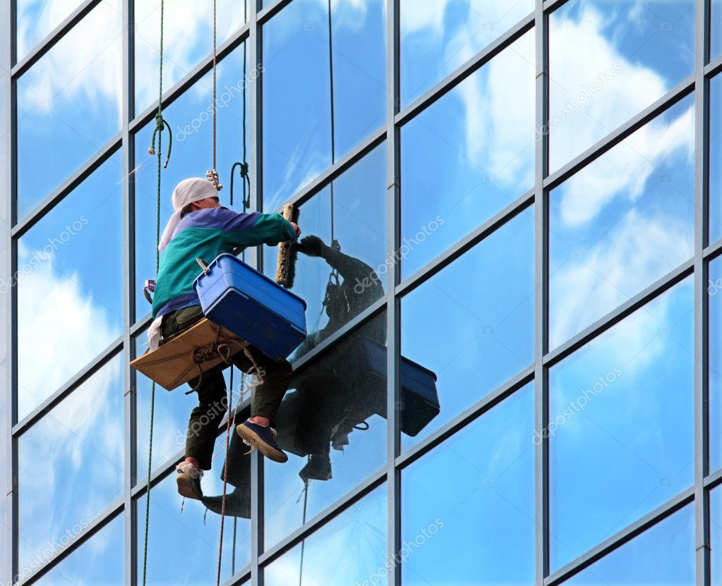 Window cleaner hanging on rope at work on skyscraper for 2 good guys window cleaning