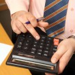 Businessman counts money on calculator - Stock fotografie