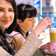 Two girls drinking cappuccino - Stock Photo