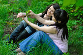 Two sisters sitting on the grass — Stock Photo