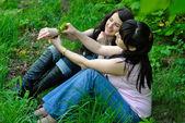 Två systrar sitter på gräset — Stockfoto